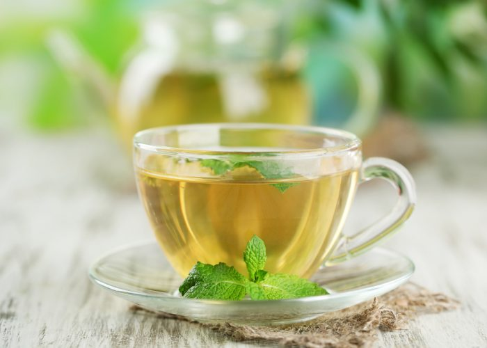 Травяной чай с листочком мяты на блюдце