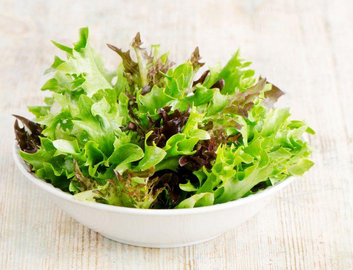 Зеленый салат в белой тарелке