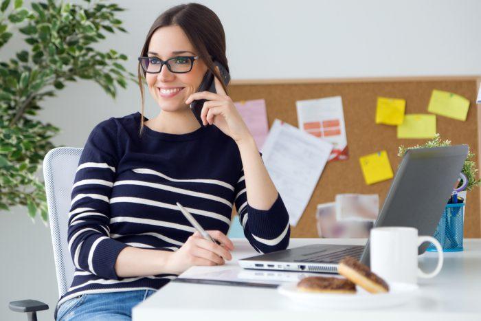 Девушка в полосатой кофте говорит по телефону в офисе