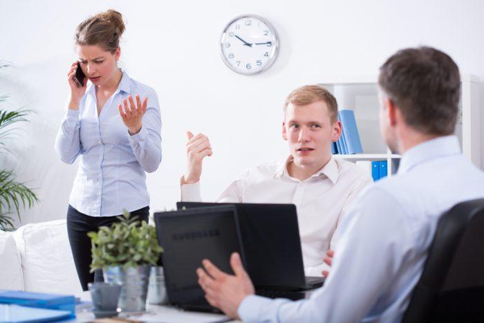 Девушка говорит по телефону возле сотрудников в офисе