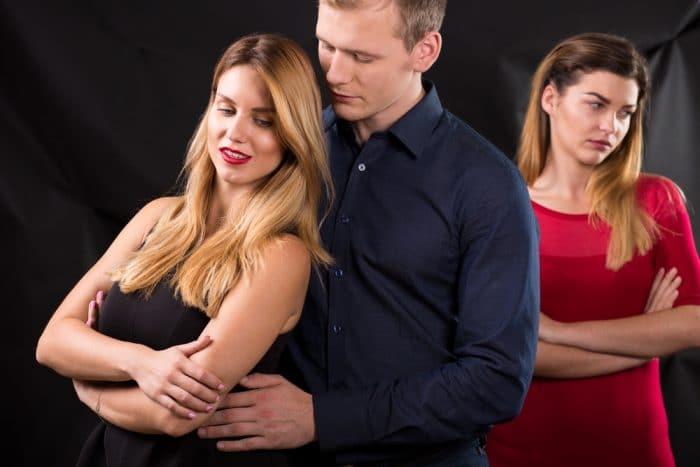 Девушка в красном платье стоит сзади пары