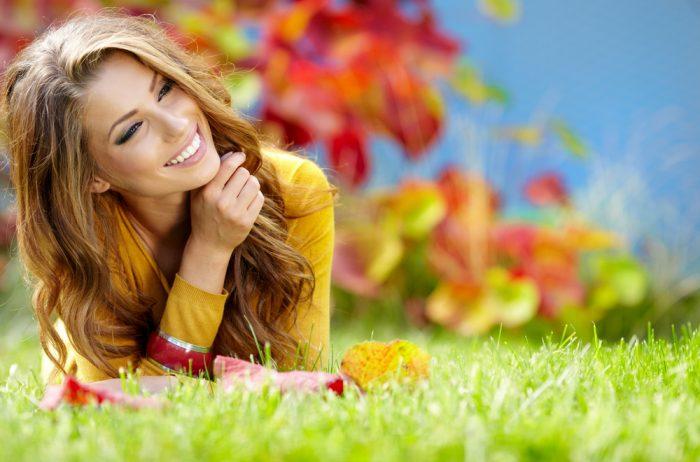 Девушка в желтой кофте лежит на траве