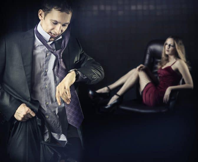 Мужчина смотрит на часы на фоне девушки в коротком платье