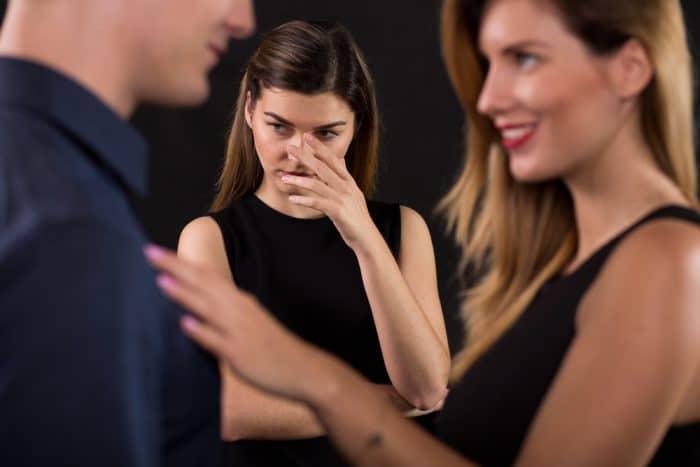 Пара говорит на фоне другой девушки