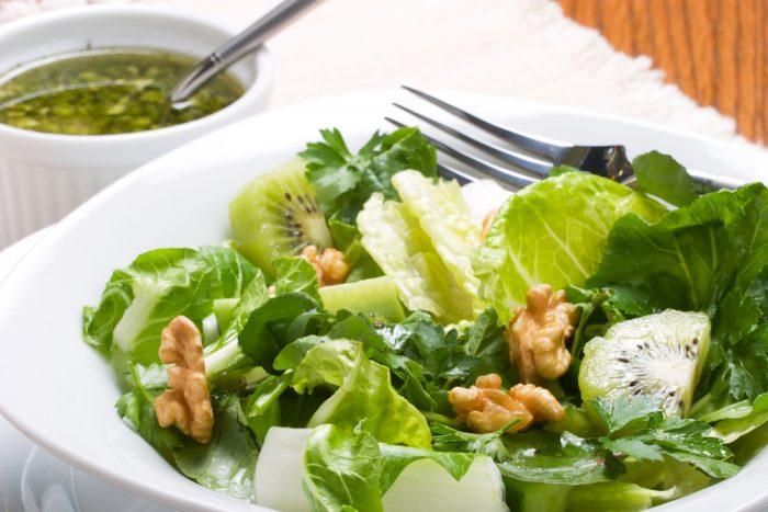 Салат из листьев, киви и орехов в белой тарелке
