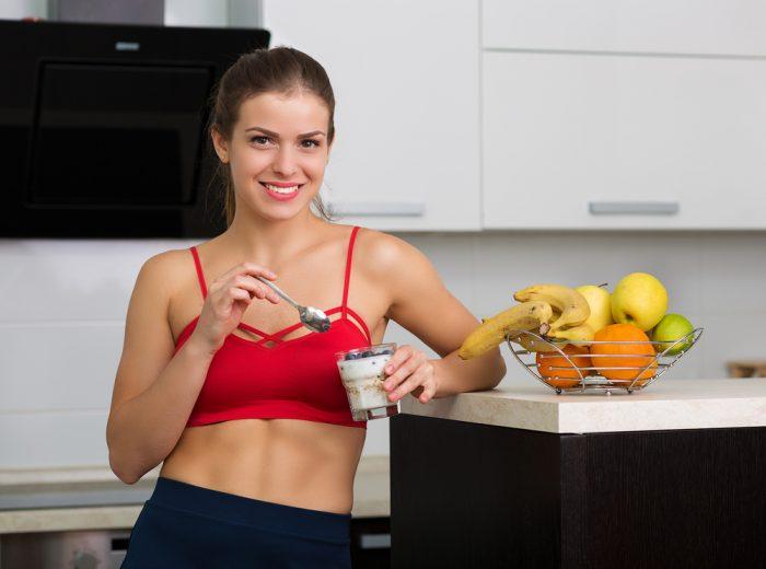 Девушка в красном топе ест йогурт