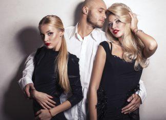Ьужчина в белой рубашке с двумя девушками