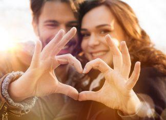 Парень с девушкой сложили пальцы в форме сердца