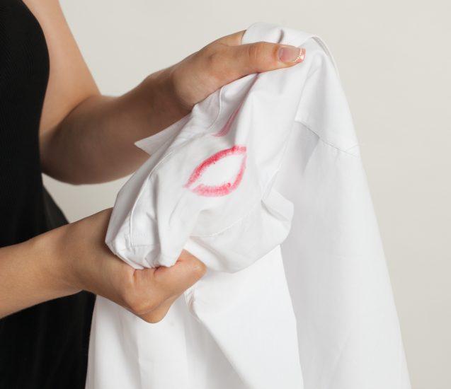 Женщина держит рубашку со следом помады