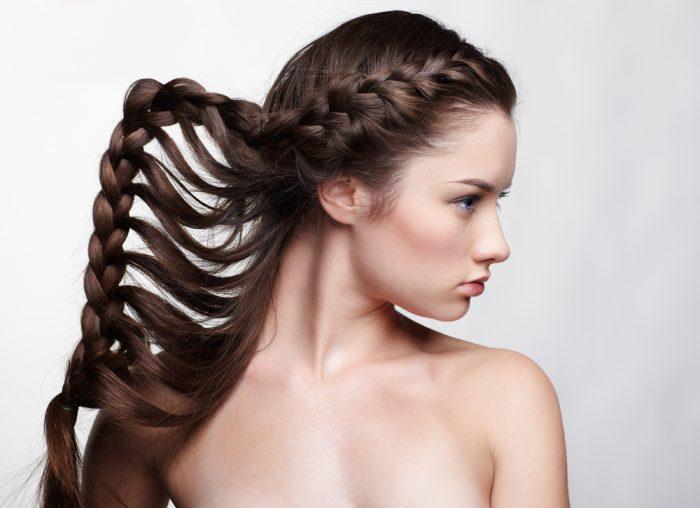 Девушка с плетенной необычной косой на сером фоне