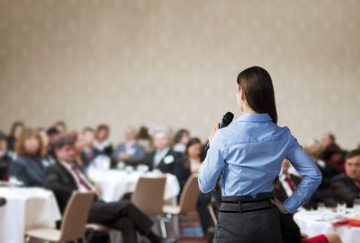 девушка в голубой рубашке говорит в микрофон перед людьми