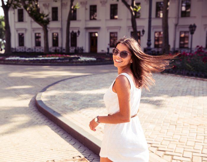 Девушка идет по улице в белом платье, в очках