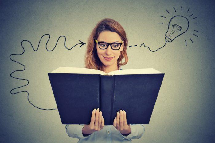 Девушка на сером фоне смотрит в книгу