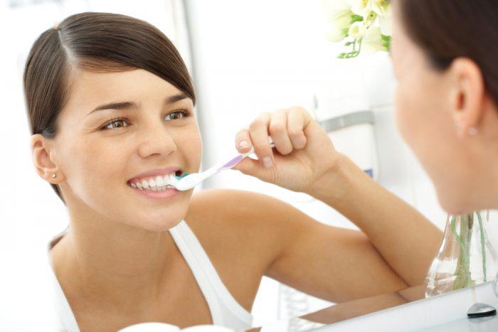 Девушка перед зеркалом чистит зубы