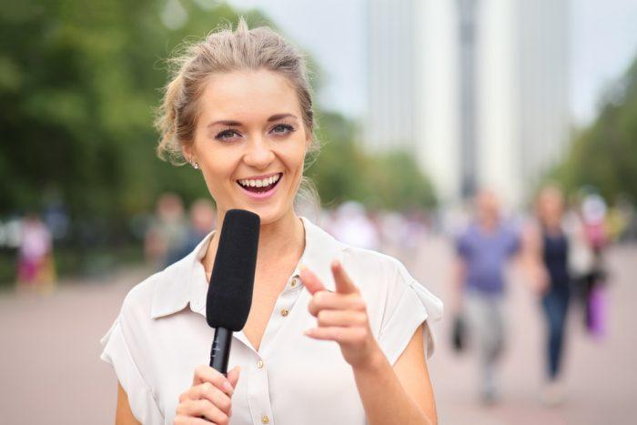Девушка в белой безрукавке на улице говорит в микрофон