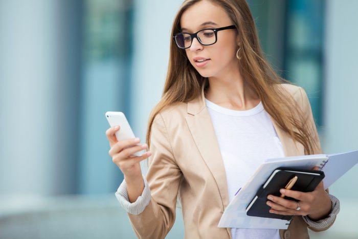 Девушка в очках смотрит на телефон