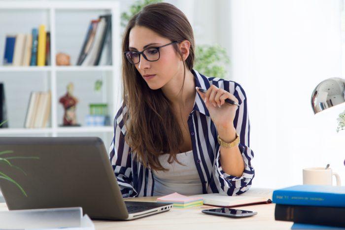 Девушка в очках и полосатой рубашке перед ноутбуком