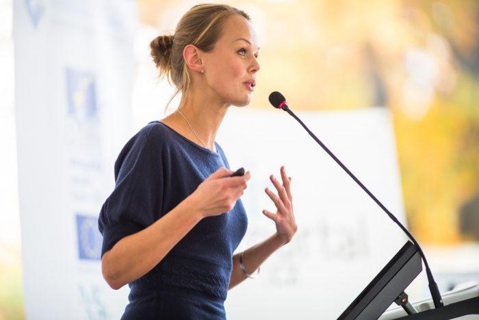 Девушка с синей кофте перед микрофоном
