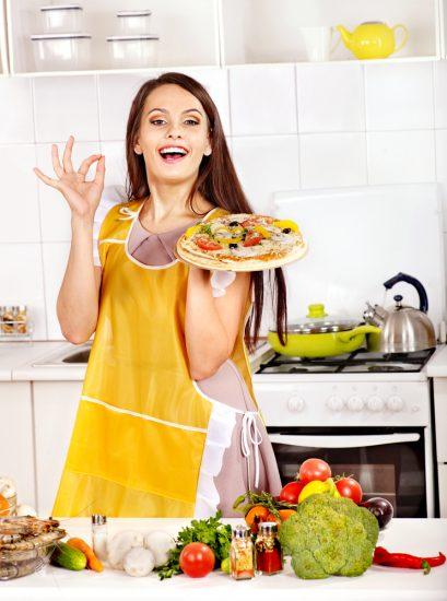 Девушка в желтом фартуке и с пиццой