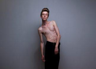 Худой парень без рубашки на сером фоне