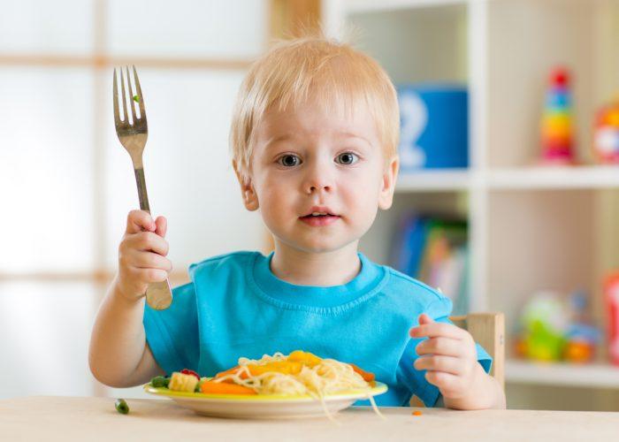 Мальчик с вилкой сидит перед тарелкой еды