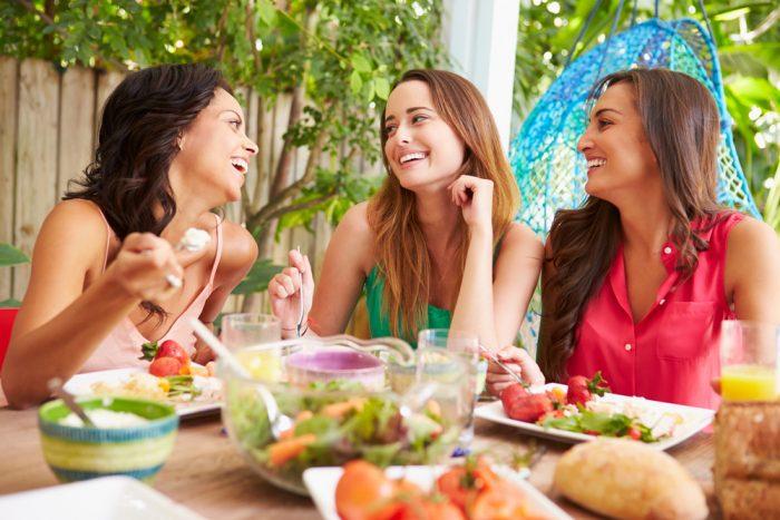 Три девушки смеются за обедом
