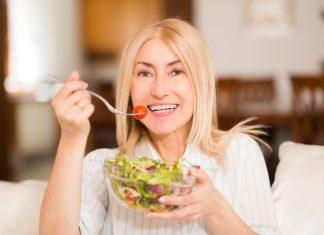 Женщина в светлой блузке ест салат