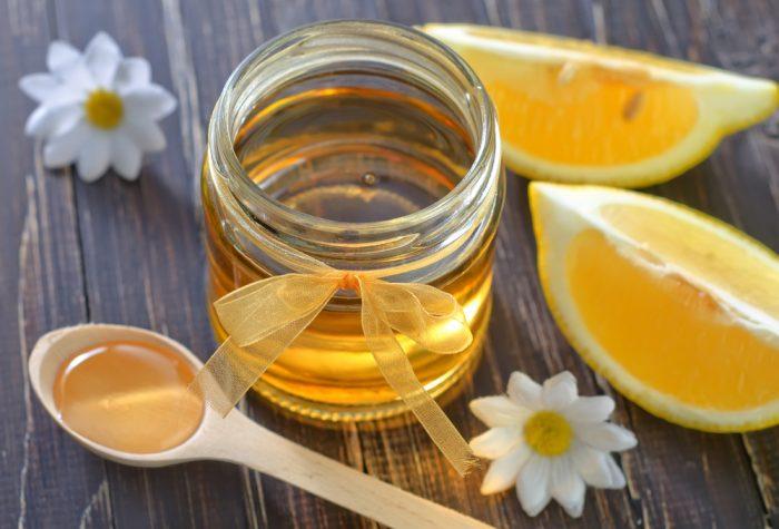 Банка с медом возле лимона,деревянной ложки и цветков ромашки
