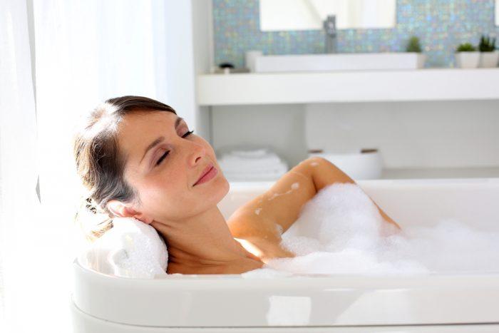 Девушка лежит в ванне с пенной