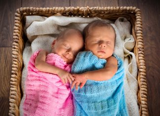 Двойняшки под розовыми голубым покрывалом спят в корзинке