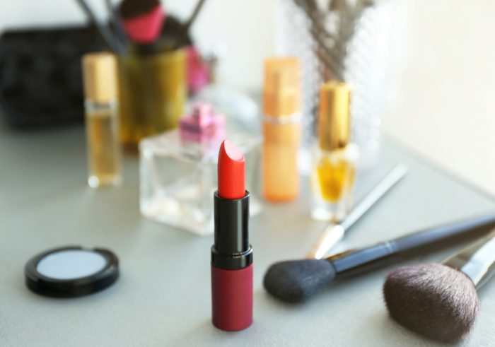 Красная помада на фоне косметики