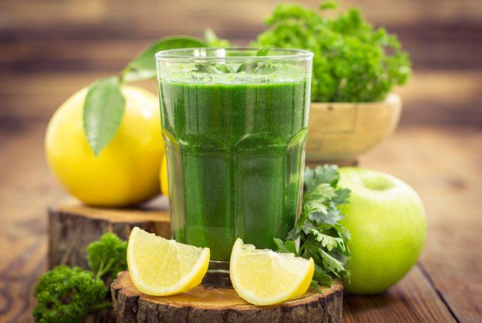 Зеленый сок в стакане возле зелени, лимона, яблока