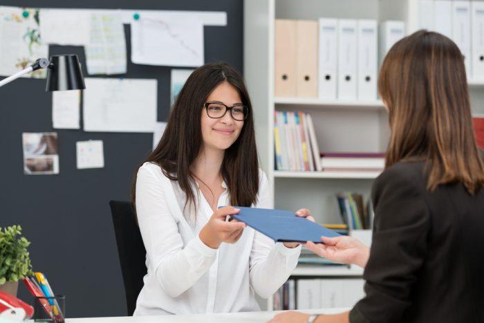 Девушка в офисе дает голубую папку начальнице