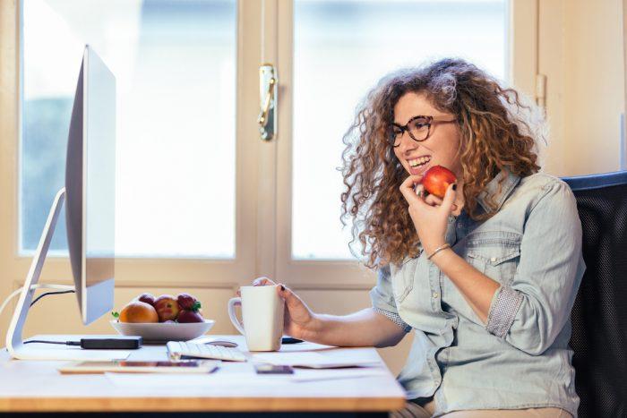 Девушка сидит за столом перед компьютером с яблоком и улыбается