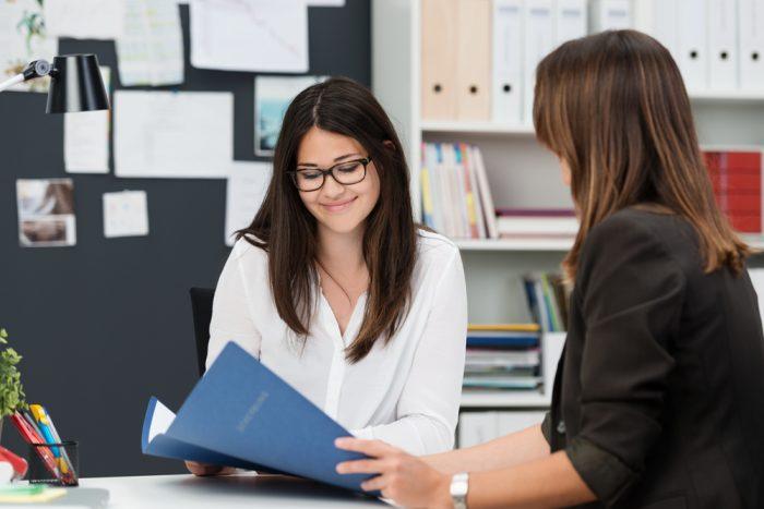 Двое молодых коллег по работе обсуждают документы за столом в офисе