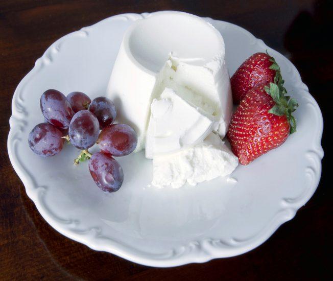 Сыр на тарелке с виноградом и клубникой