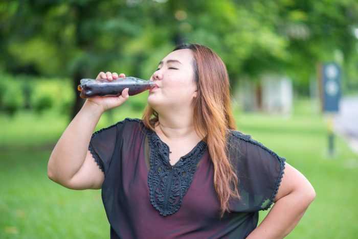 Плотная девушка пьет газировку