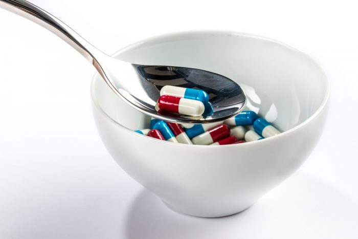 Белая тарелка с ложкой с таблетками