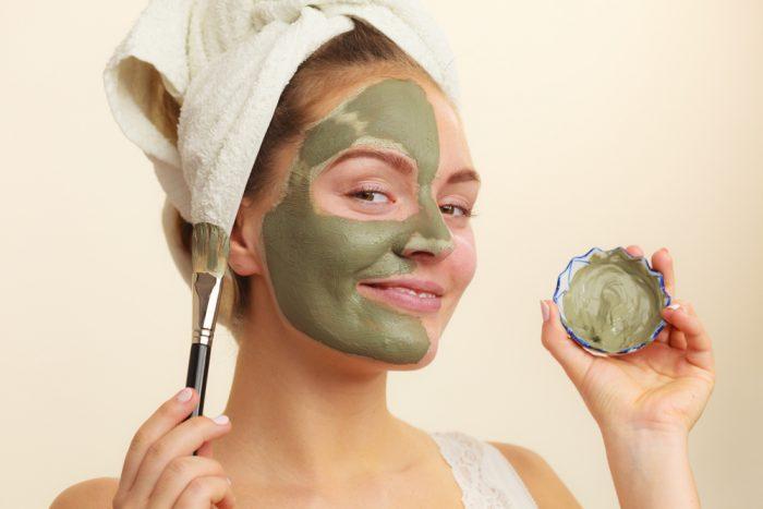 Девушка наносит на лицо зеленый скраб