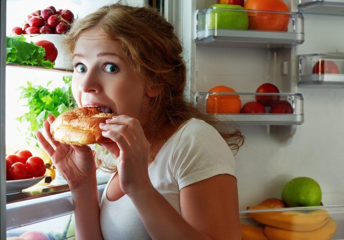 Девушка ест при открытом холодильнике