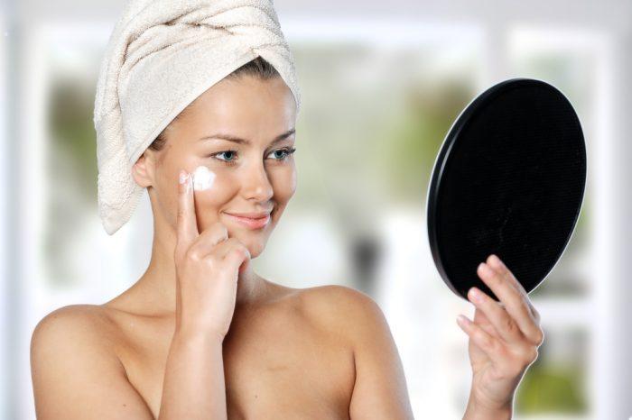 Девушка с полотенцем на голове наносит перед зеркалом крем на лицо