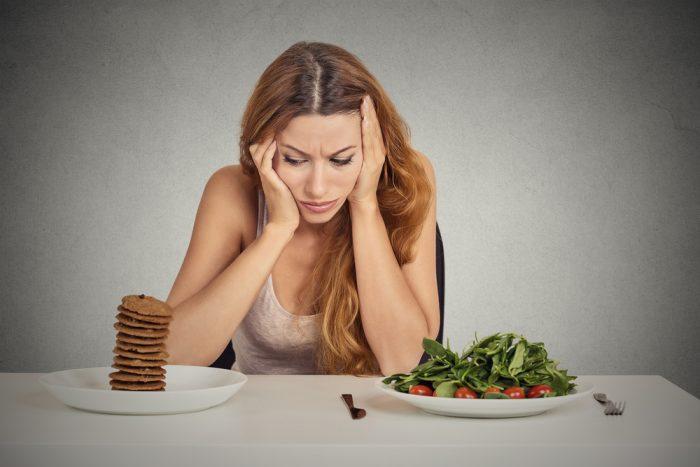 Девушка сидит перед тарелкой салата ипеченья