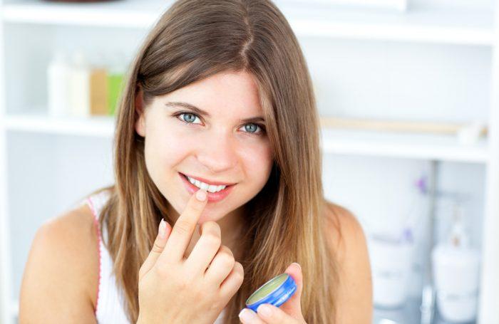 Девушка с синим бальзамом увлажняет губы
