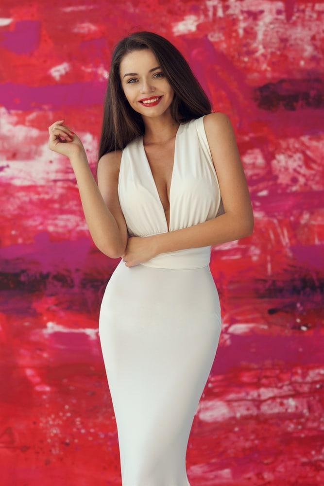 Девушка в белом платье на розовом фоне