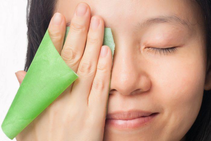 Девушка вытирает лицо зеленой салфеткой