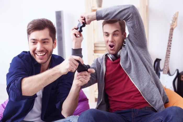 Два мужчины весело играют в видео игры
