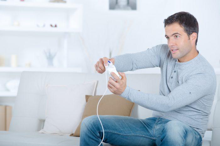 ьужчина в серой кофте и джинсах играет в видео игру