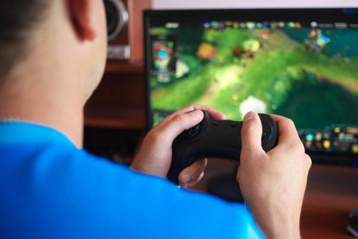 Мужчина в синей футболке играет в видео игру