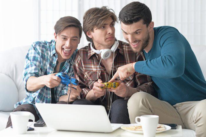 Мужчины перед белым ноутбуком играют в видео игру