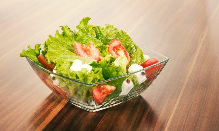 Салат с помидорами, брынзой и зеленью в прозрачной пиале на столе